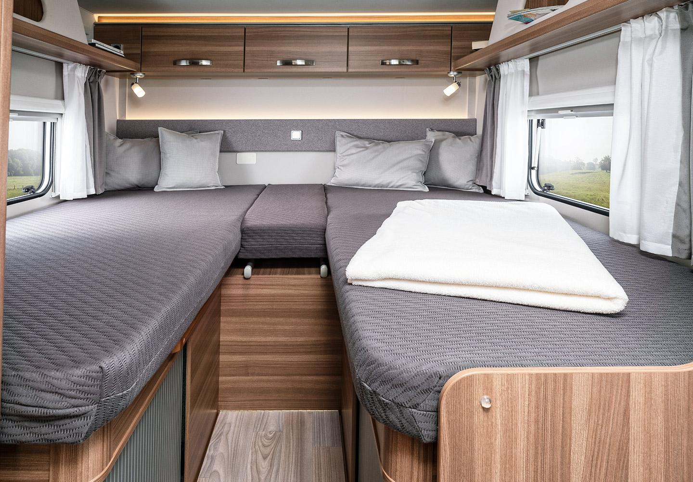 Muestra la cama doble de una caravana de alquiler